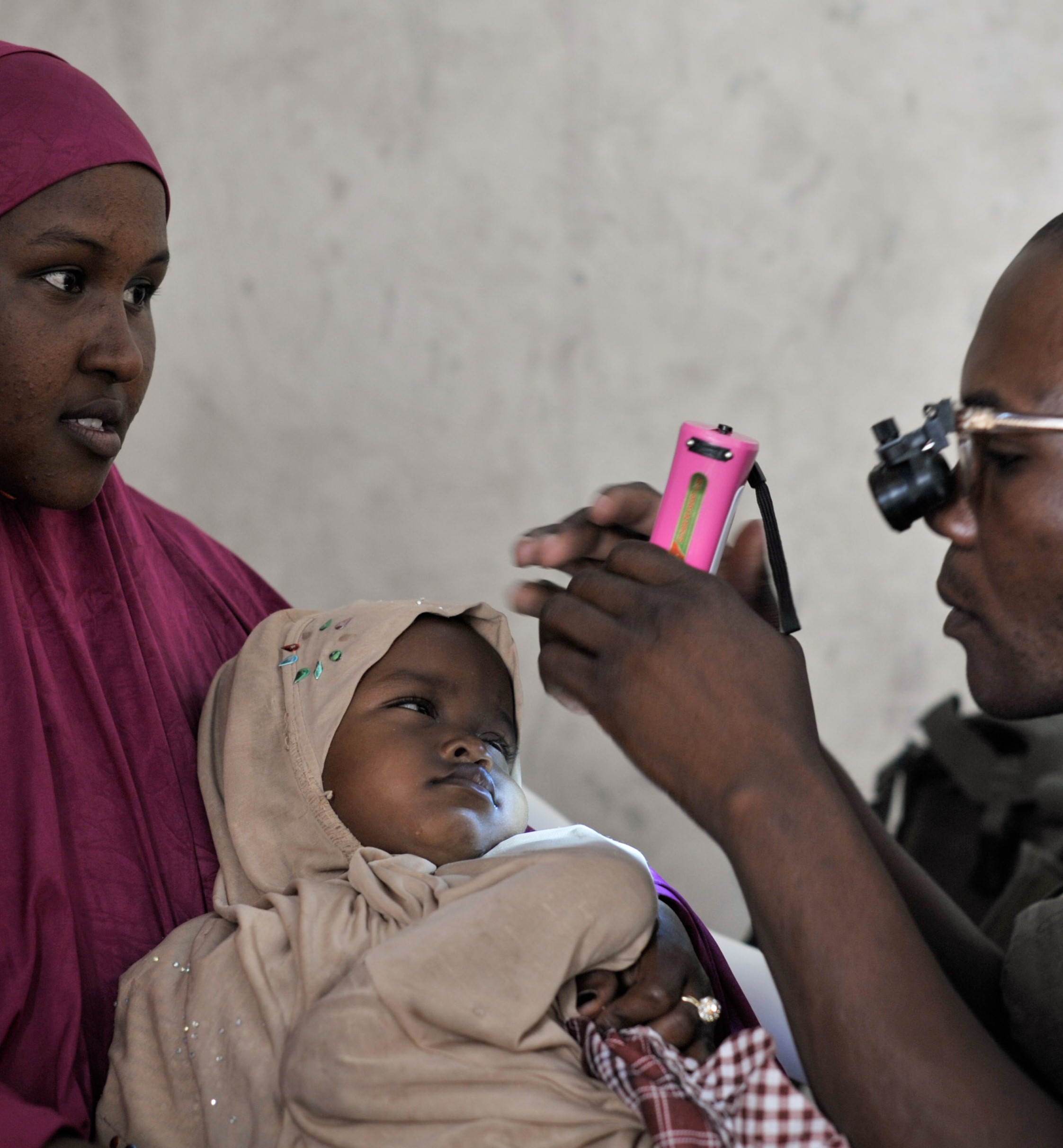 A Ugandan medic, part of the African Union Mission in Somalia (AMISOM), examines a young girl's eyes during an outpatient day for civilians in Mogadishu on December 11. AU UN IST PHOTO / Tobin Jones